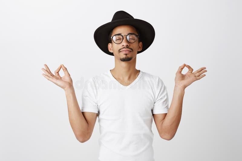 Houd kalm en draag Studioportret van ontspannen knappe Afrikaans-Amerikaanse manierontwerper in modieuze glazen en hoed stock afbeelding