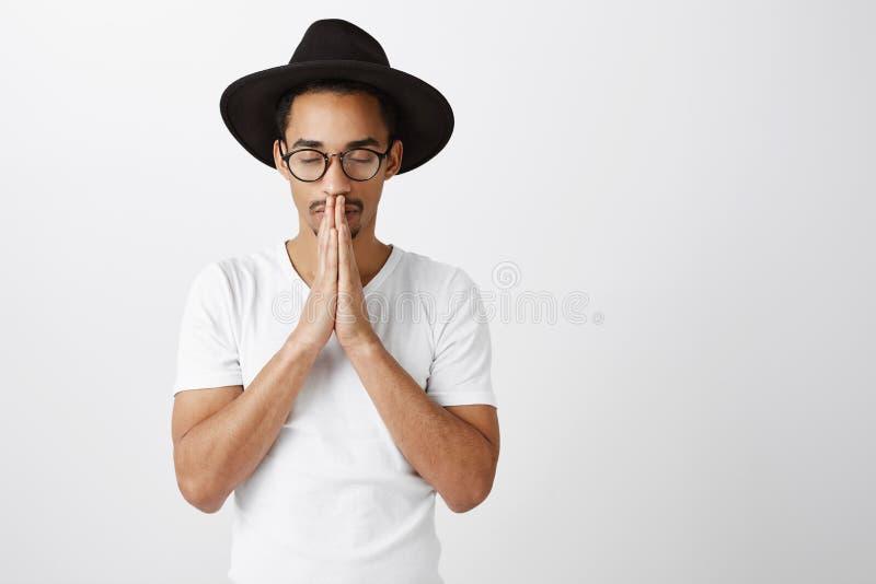 Houd kalm en geloof in mirakel Portret van geconcentreerde ernstige Afrikaans-Amerikaan in modieuze eyewear en zwarte hoed, het h stock foto's
