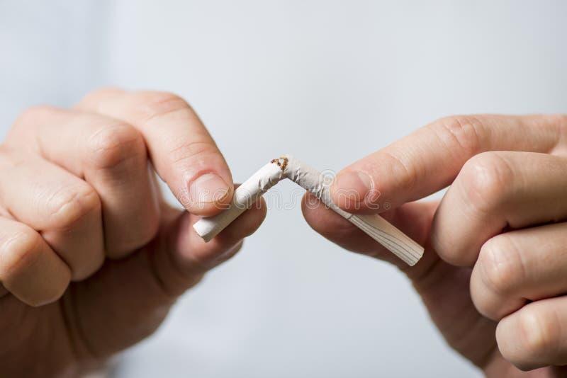 Houd met op rokend, menselijke handen die de sigaret breken royalty-vrije stock foto