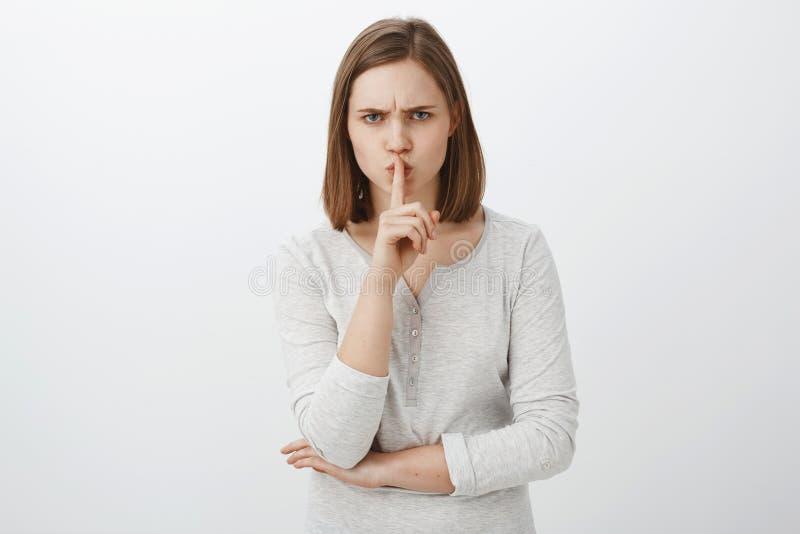 Houd mond gesloten ik verbieden vertellen iedereen mijn geheim Portret van ernstig-kijkt geïrriteerd bazig meisje met bruin haar royalty-vrije stock fotografie