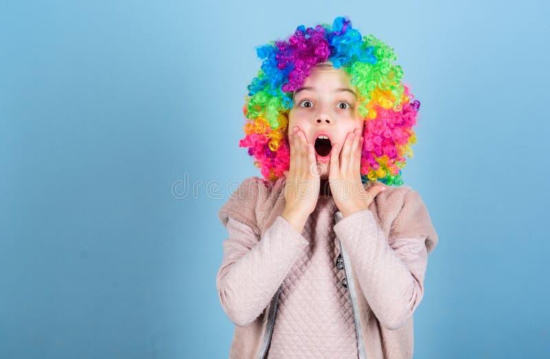 Houd uw ogen voor een verrassing Leuke kleine meisje geopende mond met grote verrassing Verrast meisje die clownhaar dragen royalty-vrije stock fotografie