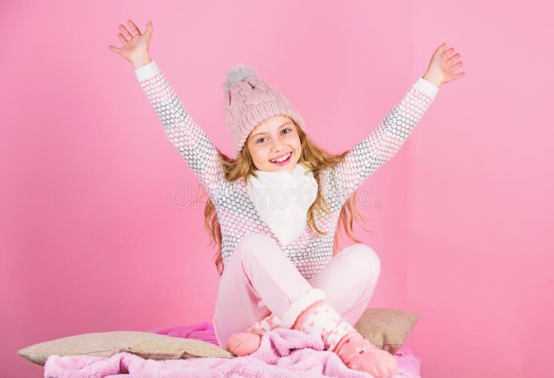 Houd warm en comfortabel De gebreide hoed die van het jong geitjemeisje slijtage roze achtergrond ontspannen Warme wollen hoed va stock afbeeldingen