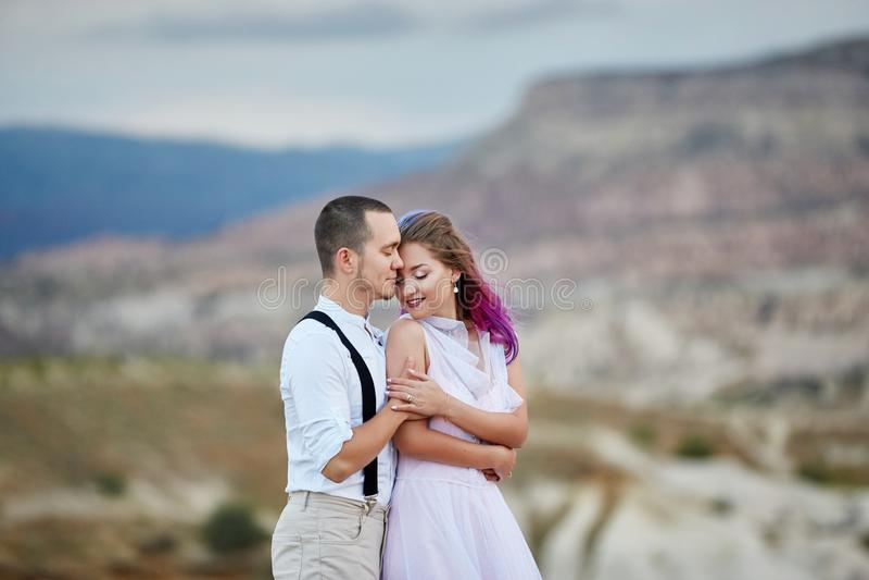 Houden het de dag houdende van paar van Valentine in aardomhelzingen en kussen, de man en de vrouw van elkaar Bergen van cappadoc royalty-vrije stock foto