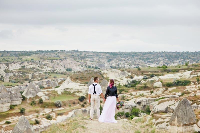 Houden het de dag houdende van paar van Valentine in aardomhelzingen en kussen, de man en de vrouw van elkaar Bergen van cappadoc stock foto