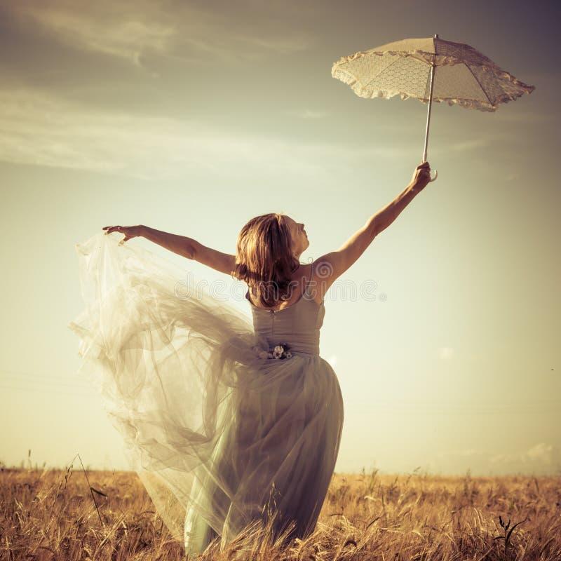 Houdend de witte mooie blonde jonge vrouw die van de kantparaplu lange blauwe balkleding dragen en omhoog op tarwegebied leunen stock fotografie