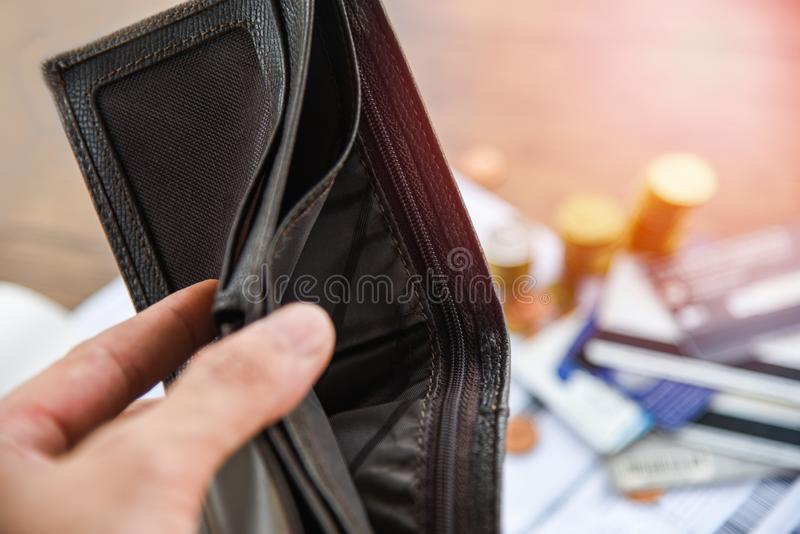 Houdend een lege portefeuille in hand en het Muntstuk, rekening, creditcardschuld verhoogde aansprakelijkheden - geen geldconcept stock afbeelding