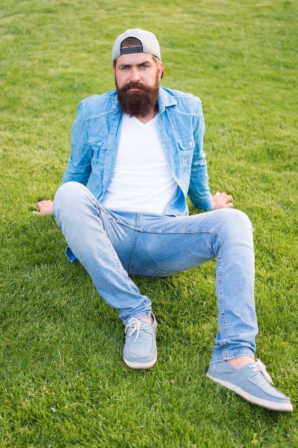 Houdend het toevallig Gebaarde mens in toevallige en op z'n gemak uitrustingszitting op groen gras Hipster in toevallige denimsti royalty-vrije stock afbeelding