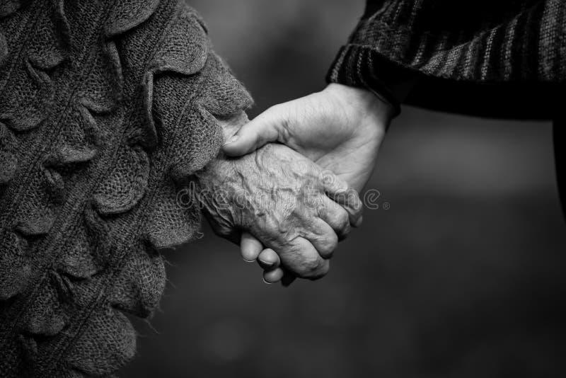 Houdend twee mensenhanden jong en oud stock afbeeldingen