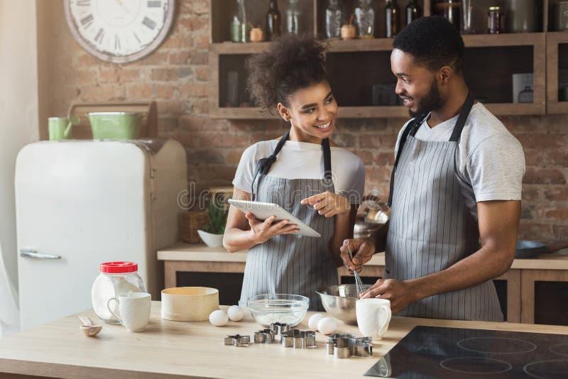 Houdend van Afrikaans-Amerikaans paar baksel en het gebruiken van tablet stock fotografie