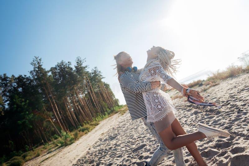Houdend van de blonde-haired mens die zijn modieuze vrouw koesteren die rust op strand hebben stock foto's