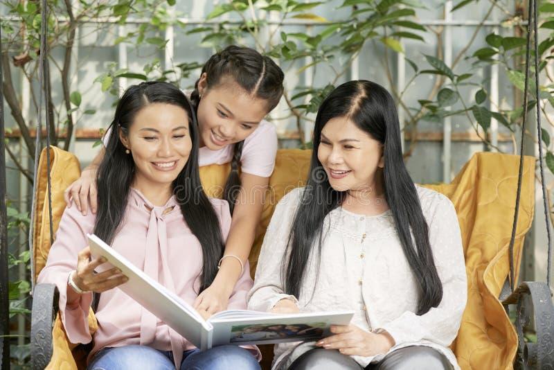 Houdend van etnische vrouwen die van familie foto's kijken stock afbeeldingen