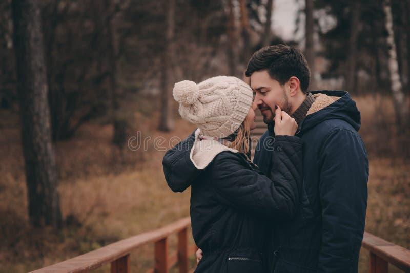 Houdend van het jonge paar kussen openlucht op comfortabele warme gang in bos stock fotografie