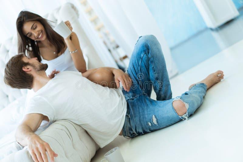 Houdend van jong paar die en op bank thuis koesteren ontspannen royalty-vrije stock foto's