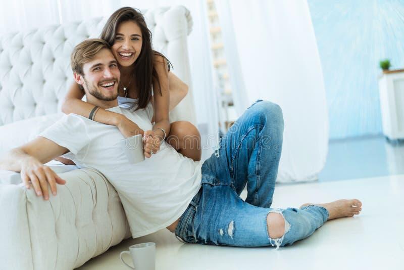 Houdend van jong paar die en op bank thuis koesteren ontspannen royalty-vrije stock fotografie