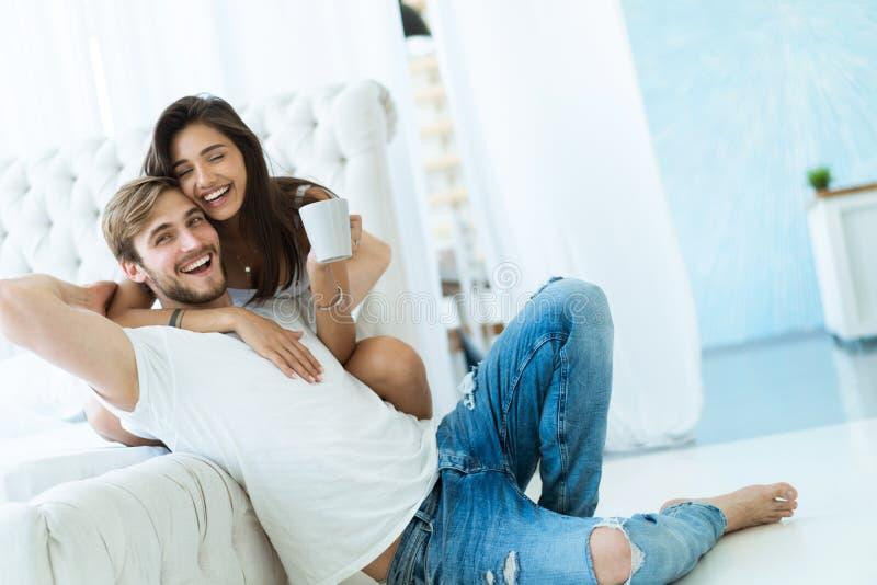Houdend van jong paar die en op bank thuis koesteren ontspannen stock afbeelding