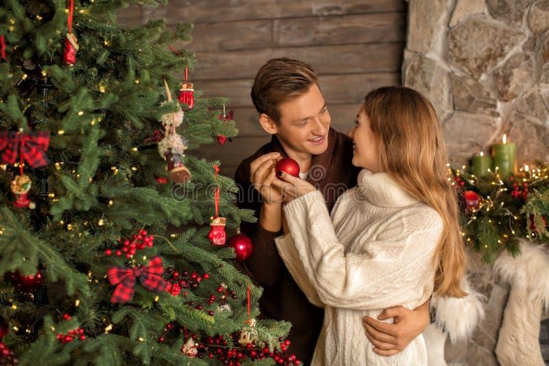 Houdend van jong paar die Kerstboom thuis verfraaien royalty-vrije stock foto