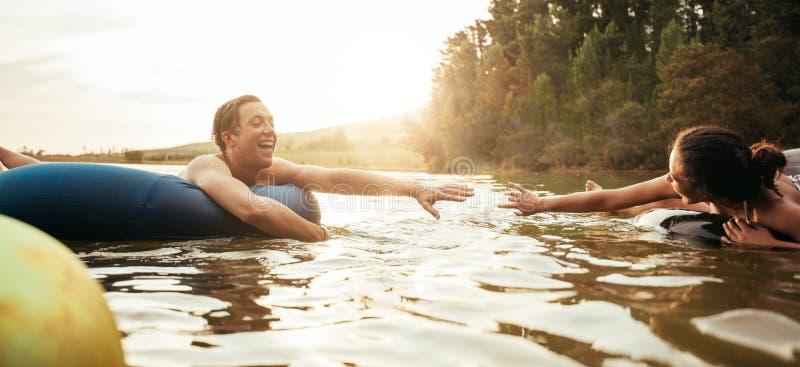 Houdend van jong paar die pret in het meer hebben stock afbeeldingen