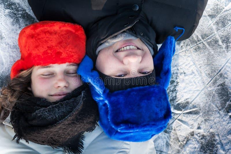 Houdend van jong paar die pret op sneeuw met ijsachtergrond hebben tijdens Kerstmisvakantie stock foto