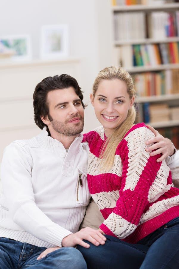 Houdend van jong paar die thuis ontspannen royalty-vrije stock afbeelding