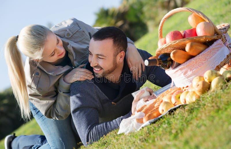 Houdend van mooi paar die zoals hebbend picknick babbelen royalty-vrije stock afbeeldingen