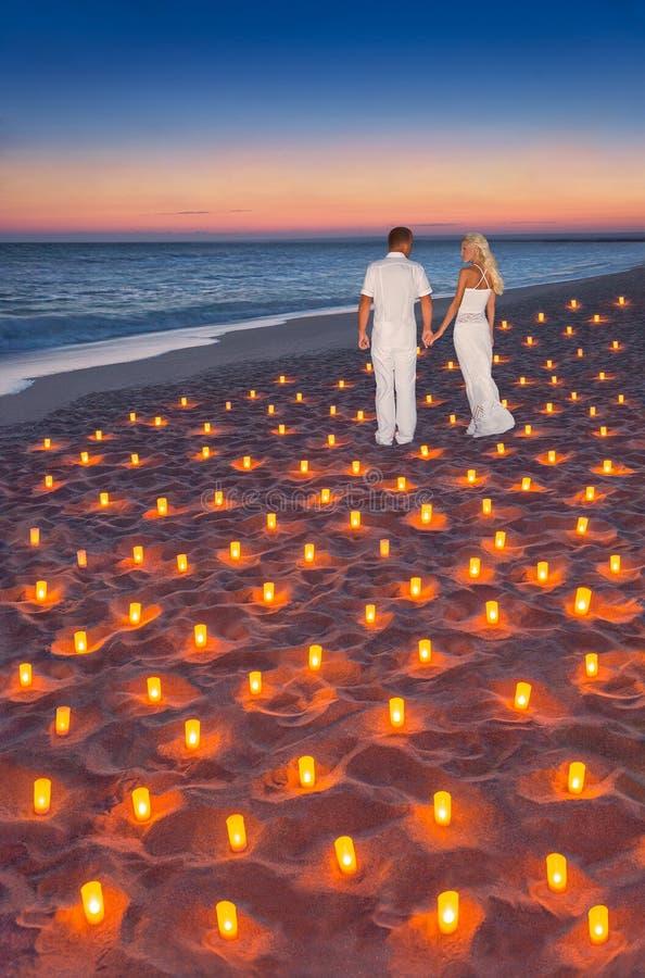 Houdend van paar bij tropisch zonsondergang oceaan zandig strand met partij van c stock fotografie