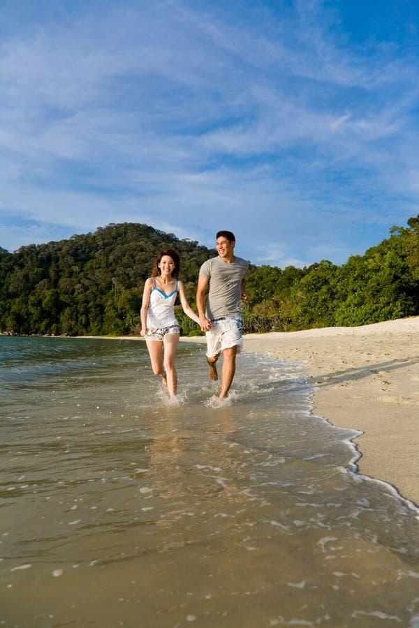 Houdend van paar dat langs het strand loopt royalty-vrije stock fotografie