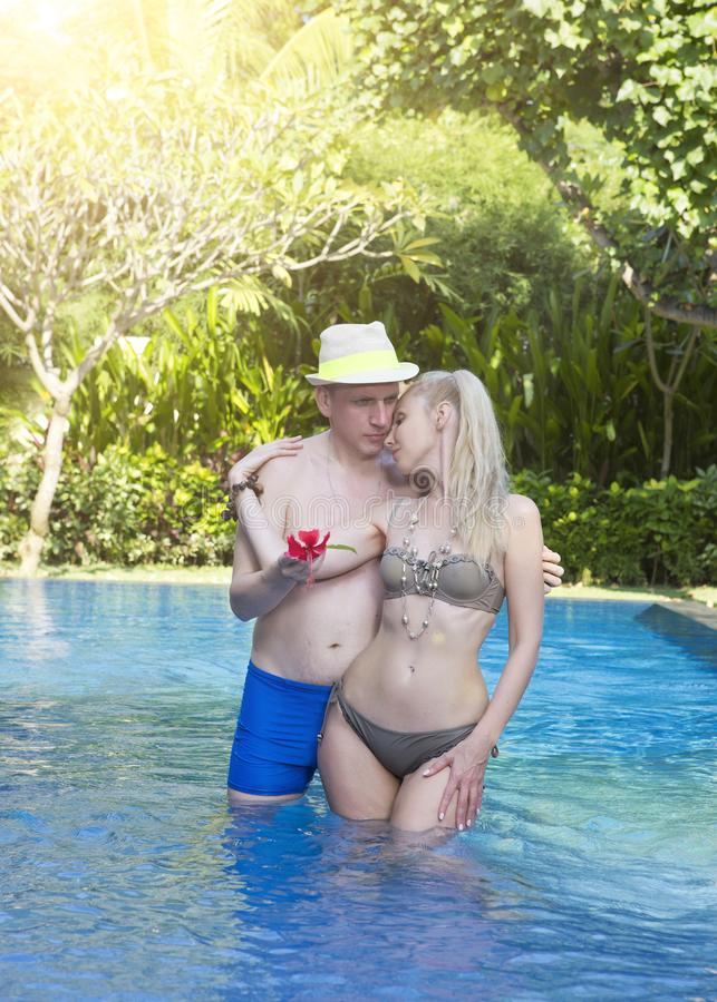 Houdend van paar in de pool in een tuin met tropische bomen De man omhelst de vrouw stock foto