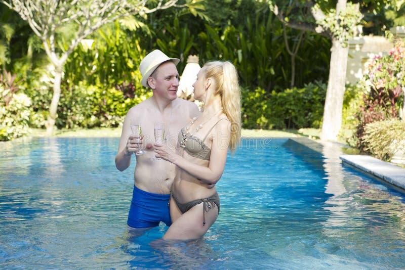 Houdend van paar in de pool in een tuin met tropische bomen De man omhelst de vrouw royalty-vrije stock fotografie