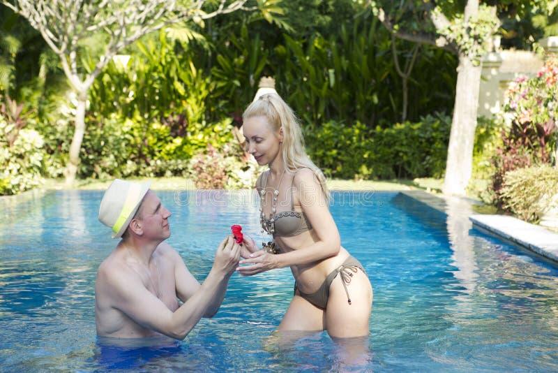 Houdend van paar in de pool in een tuin met tropische bomen De man omhelst de vrouw royalty-vrije stock foto's