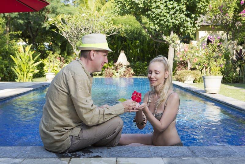 Houdend van paar in de pool in een tuin met tropische bomen De man omhelst de vrouw royalty-vrije stock afbeeldingen