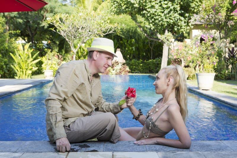 Houdend van paar in de pool in een tuin met tropische bomen De man omhelst de vrouw stock afbeelding