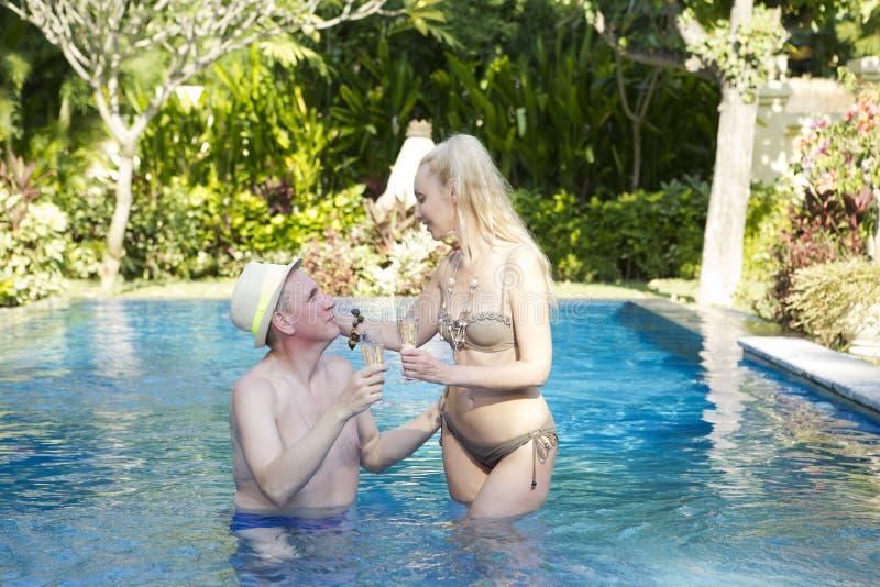 Houdend van paar in de pool in een tuin met tropische bomen De man omhelst de vrouw royalty-vrije stock afbeelding