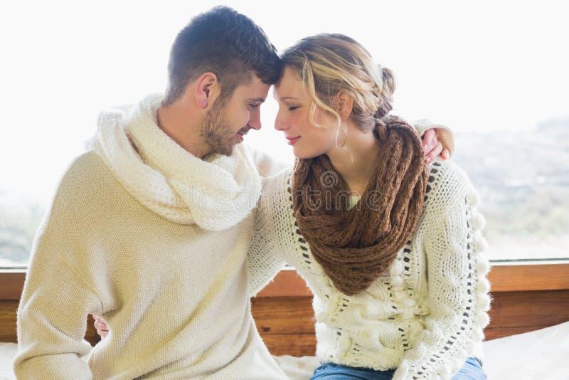 Houdend van paar in de winterkleding tegen venster royalty-vrije stock foto