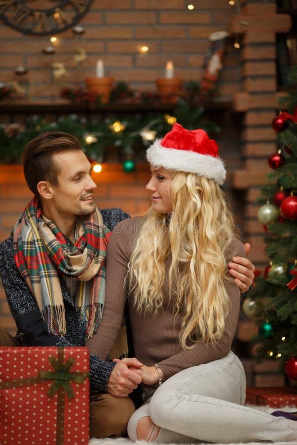 Houdend van paar dichtbij Kerstboom royalty-vrije stock foto's
