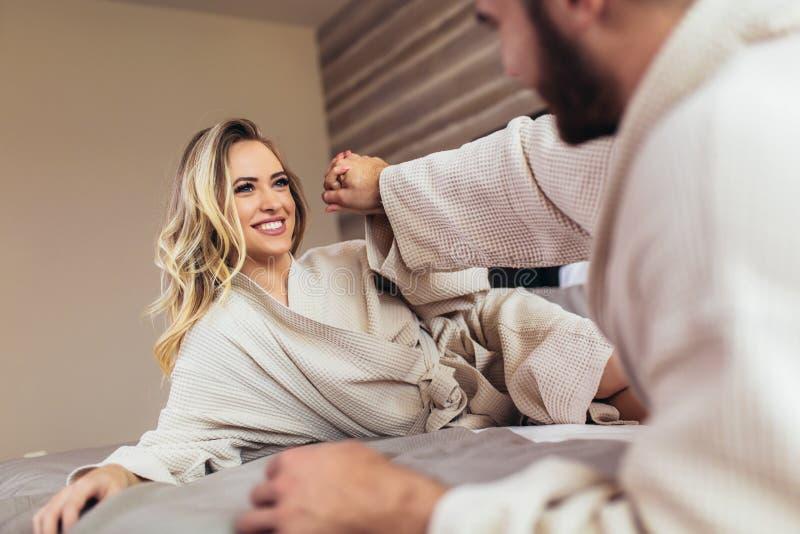 Houdend van paar die in badjassen op bed bij hotel ontspannen royalty-vrije stock fotografie