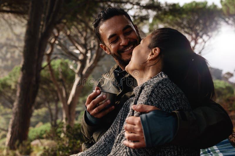 Houdend van paar die in bos en het hebben van koffie kamperen royalty-vrije stock fotografie