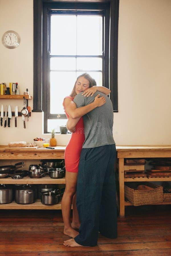 Houdend van paar die elkaar in de keuken koesteren stock foto