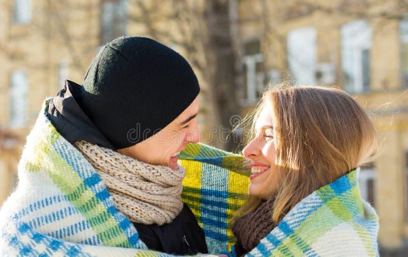Houdend van paar die elkaar en het lachen plaid in de winter bekijken De kerel koestert een meisje op de straat in de winter stock afbeelding