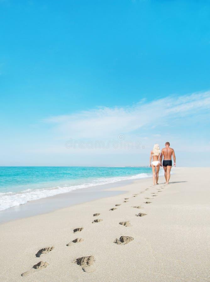 Houdend van paar die met op zee voetafdrukken lopen royalty-vrije stock fotografie