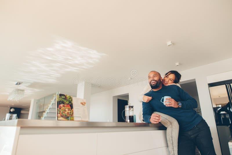 Houdend van paar die ochtend van koffie in keuken genieten royalty-vrije stock foto's