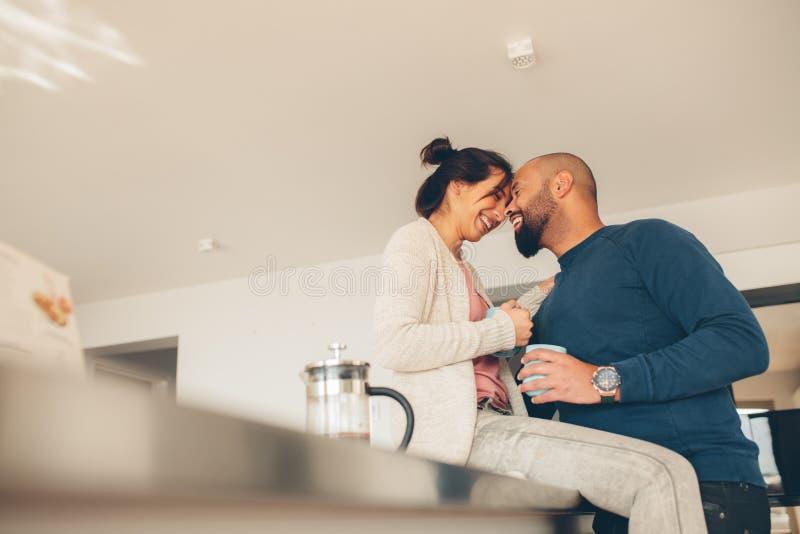 Houdend van paar die ochtend van koffie thuis genieten royalty-vrije stock afbeelding