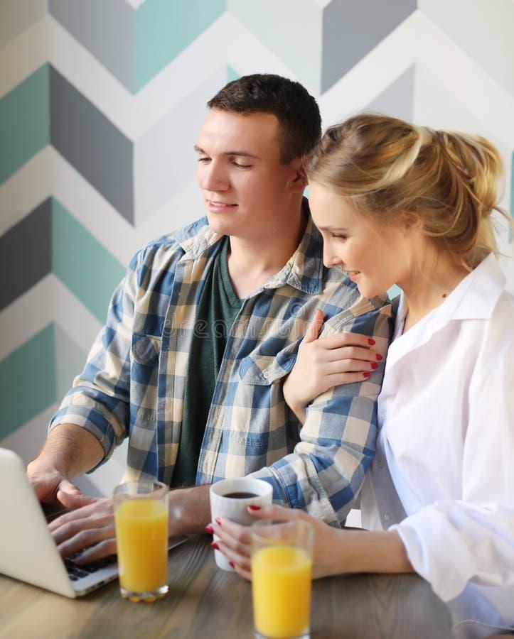 Houdend van paar die ontbijt hebben en laptop computer bekijken royalty-vrije stock fotografie
