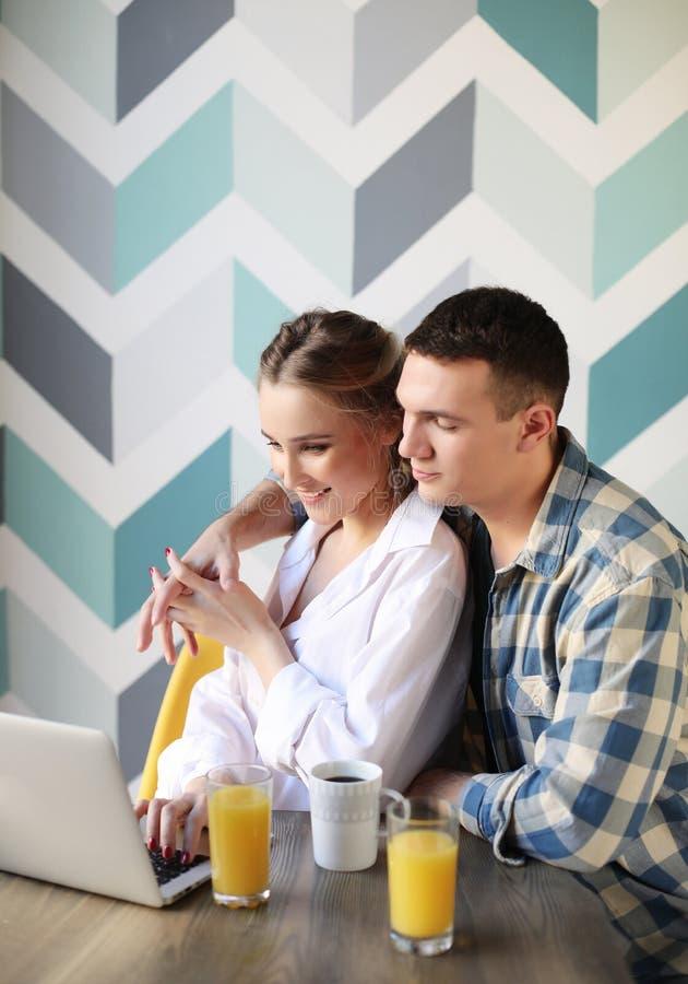 Houdend van paar die ontbijt hebben en laptop computer bekijken royalty-vrije stock afbeelding