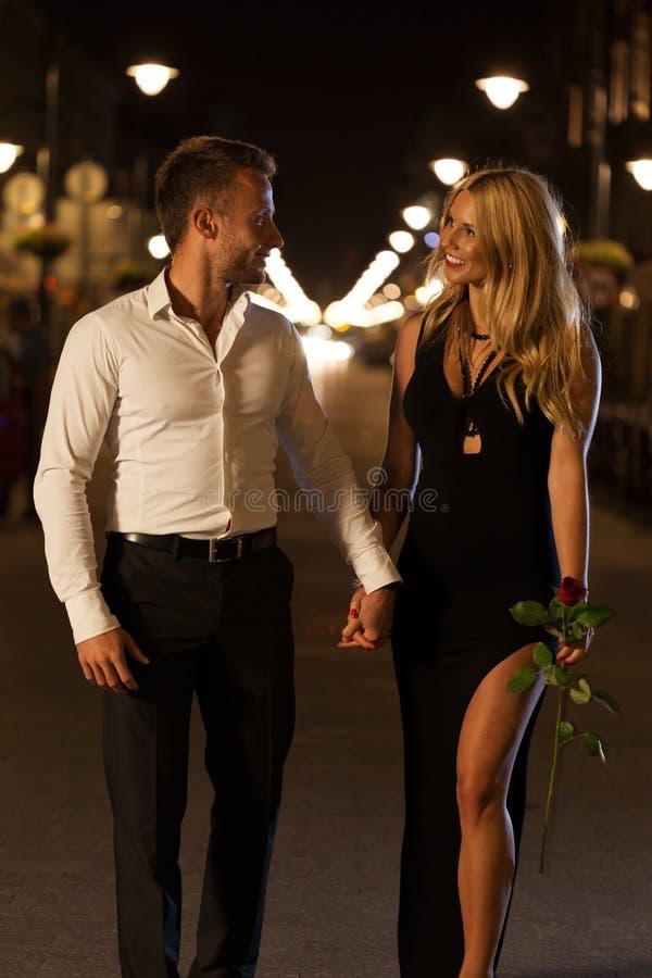 Houdend van paar die op de straat lopen stock fotografie