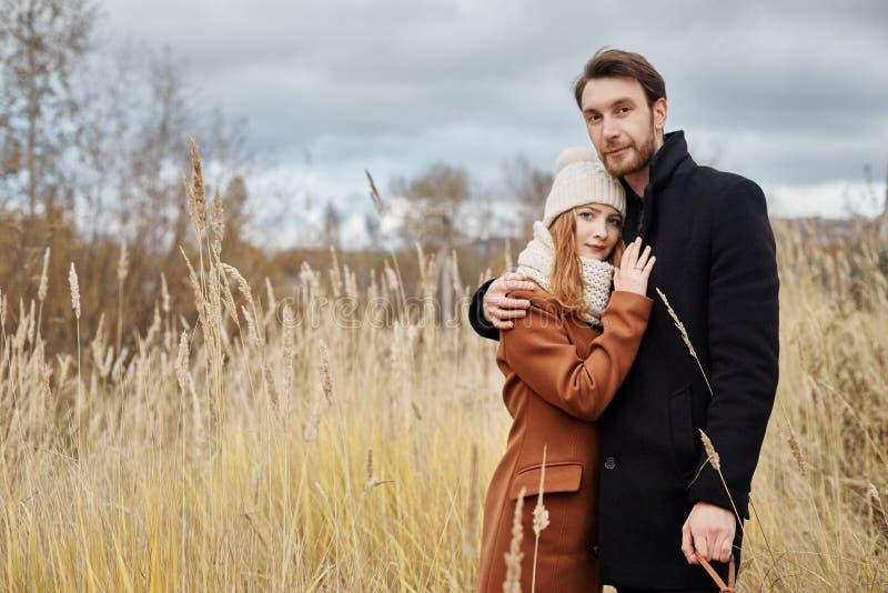 Houdend van paar die op het gebied, de herfstlandschap omhelzen Man en vrouw in de herfstkleren in aard, liefde en tederheid in a stock foto