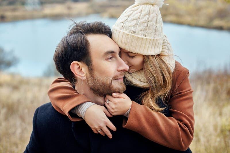Houdend van paar die op het gebied, de herfstlandschap omhelzen Man en vrouw in de herfstkleren in aard, liefde en tederheid in a royalty-vrije stock foto