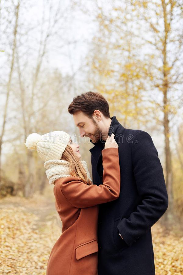 Houdend van paar die in Park in de herfstomhelzingen en kussen lopen De herfst royalty-vrije stock fotografie
