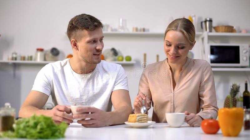 Houdend van paar die thee hebben en bij keuken communiceren, die cake, geluk eten stock fotografie