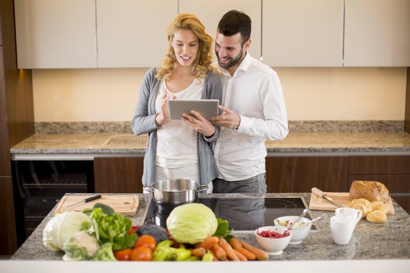 Houdend van paar die zich in de keuken met digitale tablet bevinden royalty-vrije stock foto