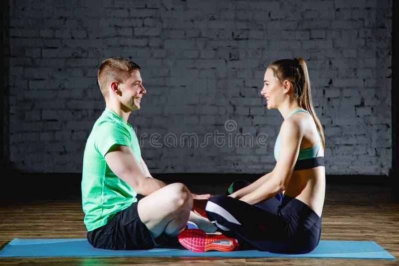Houdend van paar in gymnastiek die na de handen van de sportholding rusten royalty-vrije stock foto's
